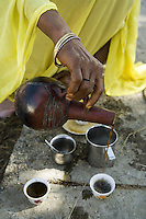 Eritrea. Anseba province. Elaberid Community hospital. Coffee ceremony. A black woman pours hot black coffee into cups. Silver and gold bracelet. © 2006 Didier Ruef