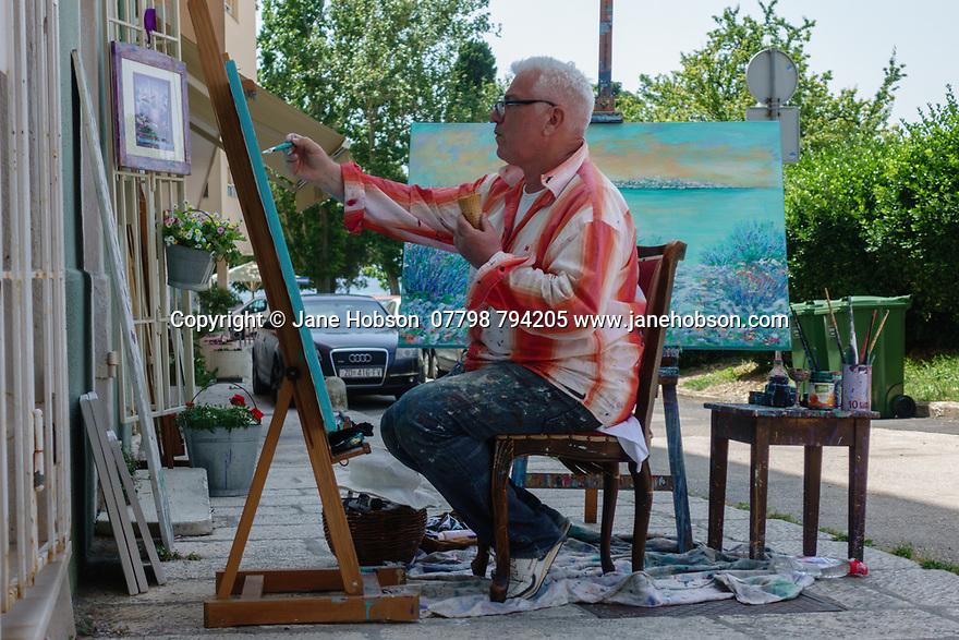 Zadar, Croatia. 31.05.2018. An artist paints outside his shop, by the Forum, Old Town, Zadar, Croatia. Photograph © Jane Hobson.