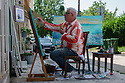 Zadar, Croatia. 31.05.2018. An artist paints outside his shop, by the Forum, Old Town, Zadar, Croatia. Photograph © Jane Hobson.
