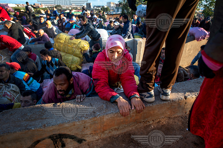 Nora El-KouKhou (centre wearing as red jacket) tries to climb a wall to escape from a stampede as hundreds of porters try to get first in line to cross the Moroccan-Spanish border. Hundreds of people work ferrying heavy loads of imported goods on their backs over the border. Melilla is a Spanish exclave on the north coast of Africa bounded by Morocco and the Mediterranean Sea. Many would-be migrants see it as the gateway to Europe which accounts for the high-level of security along its borders. However, it is also a route of entry for goods and, if they can be carried by a person (the Bario Chino gate is for pedestrians only), do not attract import taxes. Thus a micro-industry has evolved carrying huge packages of goods over the border. Once the preserve of poor women, known as 'Mule-Women', the economic crisis means more and more men are acting as porters and they aggressively seek out the limited employment opportunities.