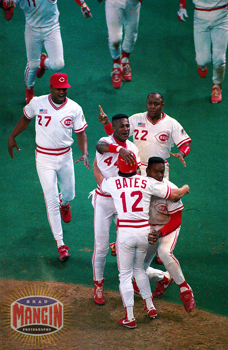 CINCINNATI, OH - Billy Bates of the Cincinnati Reds is mobbed at home plate by Eric Davis, Billy Hatcher,and Jose Rijo after scoring the game winning run in the bottom of the 10th inning in Game 2 of the 1990 World Series against the Oakland Athletics at Riverfront Stadium in Cincinnati, Ohio on october 17, 1990. Photo by Brad Mangin