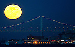 San Francisco Fisherman's Wharf and the Oakland Bay Bridge had a  full moon as a backdrop viewed from the shores of Fort Baker near the Golden Gate Bridge. ..