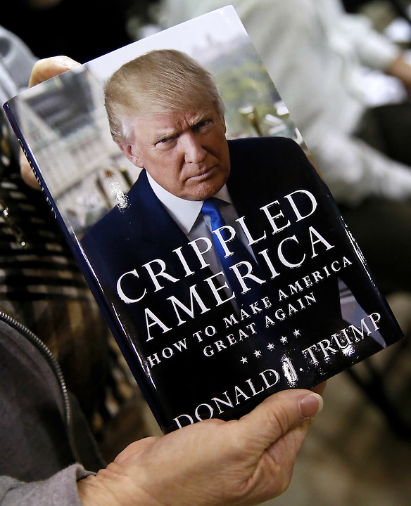A supporter of Republican U.S. presidential candidate Donald Trump shows off one of his books before a rally in Baton Rouge, Louisiana February 11, 2016. REUTERS/Jonathan Bachman