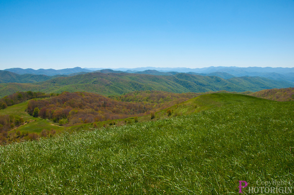 Max Patch bald mountain on a spring day, with a partly clouded blue sky.