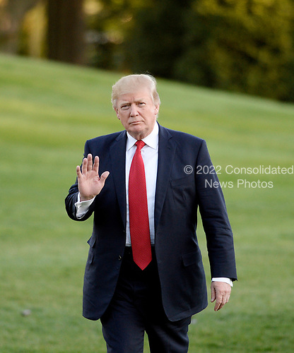 United States President Donald Trump waves to the press as he walks on the South Lawn of the White House after disembarking from Marine One in Washington, DC, April 9, 2017.<br /> Credit: Olivier Douliery / Pool via CNP