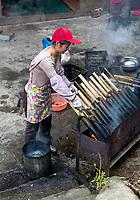 Longji, China.  Woman Cooking Sticky Rice Inside Bamboo.