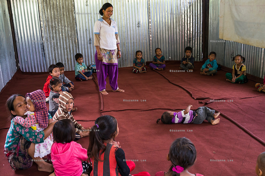 A toddler entertains everyone with his antics as the teacher looks on in the SOS Children's Villages Child Care Space in Rayale, Nepal on 1 July 2015. The Child Care Space was set up by SOS Children's Villages soon after the earthquake so that they children of the village can come together to play, learn, and get over the trauma of the disaster, while their parents can be free to reconstruct their homes and go off to get rations and relief kits. Photo by Suzanne Lee for SOS Children's Villages