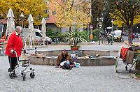Berlino, quartiere Kreuzberg. Un venditore ambulante dall'aspetto semicosciente e una anziana signora con deambulatore --- Berlin, Kreuzberg district. A street seller looking half-conscious and an old lady with walker