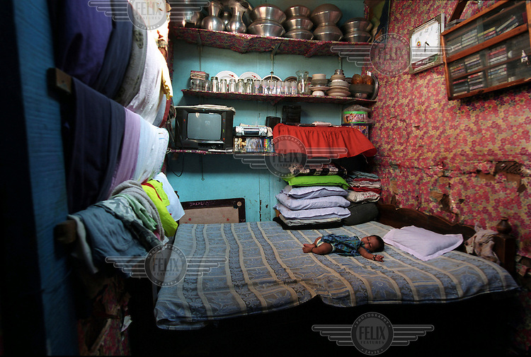A family of four share this room. The mother, having put her baby to sleep, has gone to work..Mohammadpur refugee camp is one of 66 camps for the 250,000 - 300,000 Bihari ?refugees? who were loyal to Pakistan during the fight for Bangladeshi independence in 1971. They have remained stateless and stranded in Bangladesh ever since, without citizenship for either country.