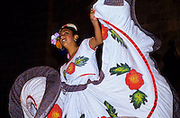 Smiling flamingo danser swinging her gown at night in Mexico