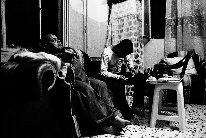 Jaddou, an Iraqi from Baghdad, sits with his son at their home in Amman, Jordan, September 2009. Photo: Ed Giles.