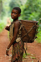 "A young girl with her basket, the ""Ykoua"", on the forest track that leads to the town.///Une jeune fille avec son panier, le « Ykoua » sur la piste forestière qui mène à la ville."