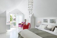 A spacious white bedroom with a Scandinavian feel with painted floorboards and a soft grey bed cover. A Catarina Larsson Nightfly pendant light hovers above the double bed, whilst two armchairs upholstered in pink and red bring a vibrant spot of colour to the room. A pair of French doors lead to a balcony beyond.