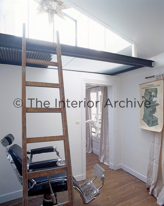 In the living room a simple wooden ladder connects a steel and wire-mesh mezzanine floor to the seating area below where an antique dentist's chair is a rather macabre option for relaxation