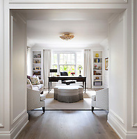 A deep open doorway leads into a traditionally styled family room, which also incorporates a study area in front of the full height windows. Comfortable seating and the cool grey and neutral colour scheme give the room a relaxing ambiance.