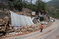 A woman stands in front of destroyed houses at Shila Porbot, outskirts of Kathmandu, Nepal. May 8, 2015