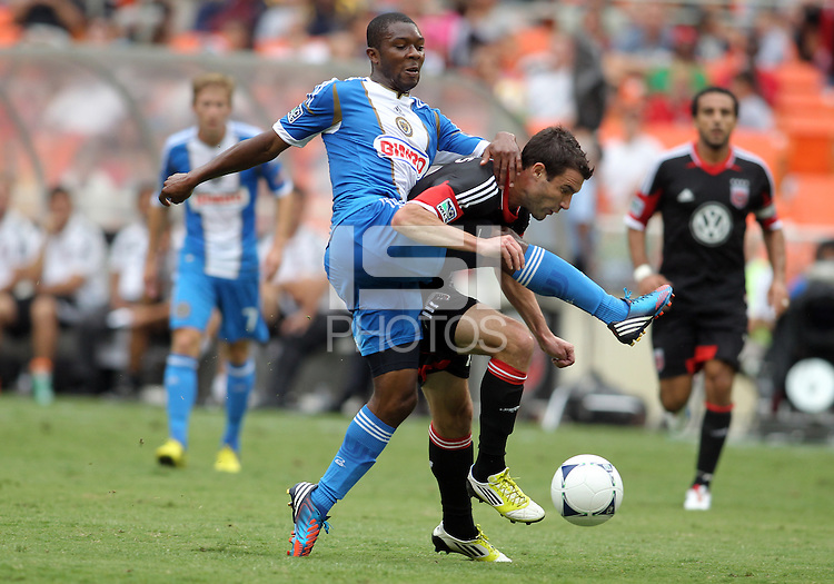 WASHINGTON, D.C. - AUGUST 19, 2012:  Chris Pontius (13) of DC United gets a hefty tackle from Amobi Okugo (14) of the Philadelphia Union during an MLS match at RFK Stadium, in Washington DC, on August 19. The game ended in a 1-1 tie.