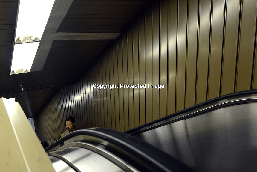 A business lady on an escalator on the Tokyo underground, Tokyo, Japan.<br /> April-2014
