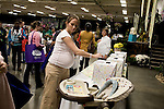 November 15, 2008. Fayetteville, NC..One thousand Army wives and active duty soldiers pregnant with what the locals call ?surge babies? were celebrated at the biggest military baby shower ever. These babies were conceived when.troops from the 82nd Airborne Division, deployed to Iraq for the surge of forces in January 2007, began returning home to Fort Bragg in November.. Nicole Mills, who is 37 weeks pregnant and in the National Guard, as well as being a military spouse, places her ticket in a box for the many items to raffled off to the attendees.