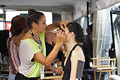 Makeup artist putting mascara on model before fashion show