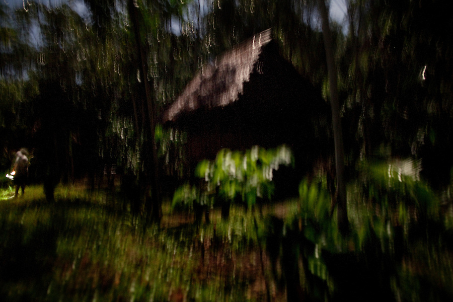 Iquitos, Peru, September 13, 2013 - A view of the jungle, a hut and guide Wellington, taken at night using only moon light over a long exposure.