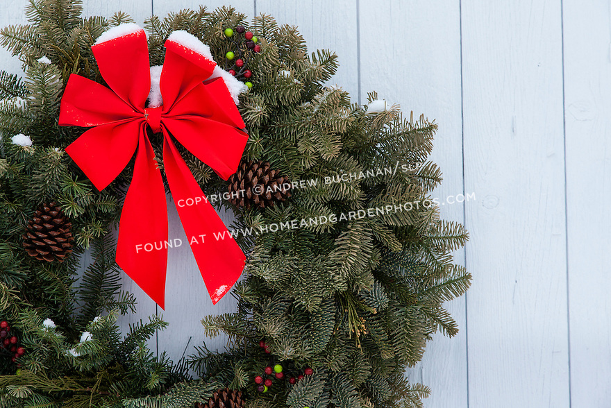 A holiday wreath with a bright red bow set against a white barn door