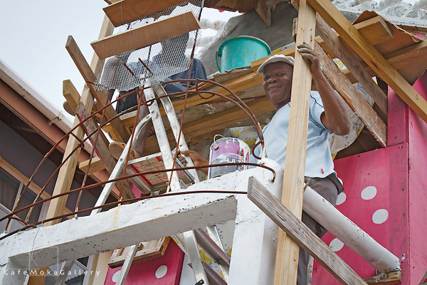 The pink and white decorative and eclectic house of Lawrence Andrews here working on his house, Portsmouth, Dominica