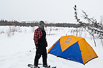 A man walks in snowshoes near a Sierra Designs tent.