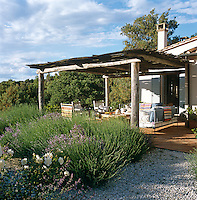The loggia looks out over lavender and white roses towards the rolling Tuscan hills