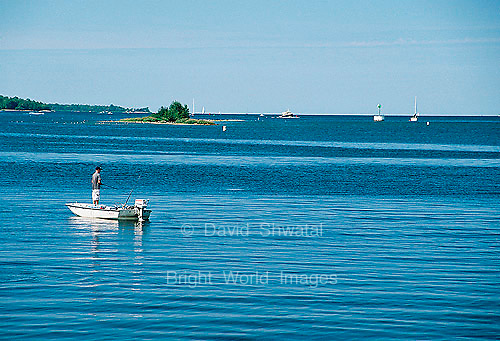 Man fishing on a boat in the blue waters of Sturgeon Bay, Lake Michigan