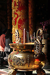 Bao-jhong Yi-min Temple, Kaohsiung -- Incense brazier with Taoist worshipers in the background.