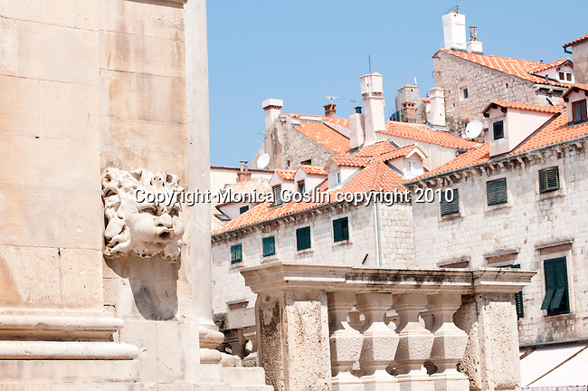 A stone face on the side of St. Blaise Church of Dubrovnik, Croatia with the red roofs of the town in the background.