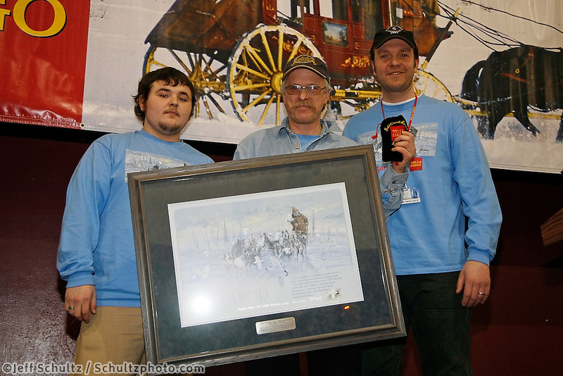 Jeff King recieves the first to the coast (Unalakleet)  award from Wells Fargo representatives Sean Ocuck & Loren Prosser  at the Nome awards banquet.