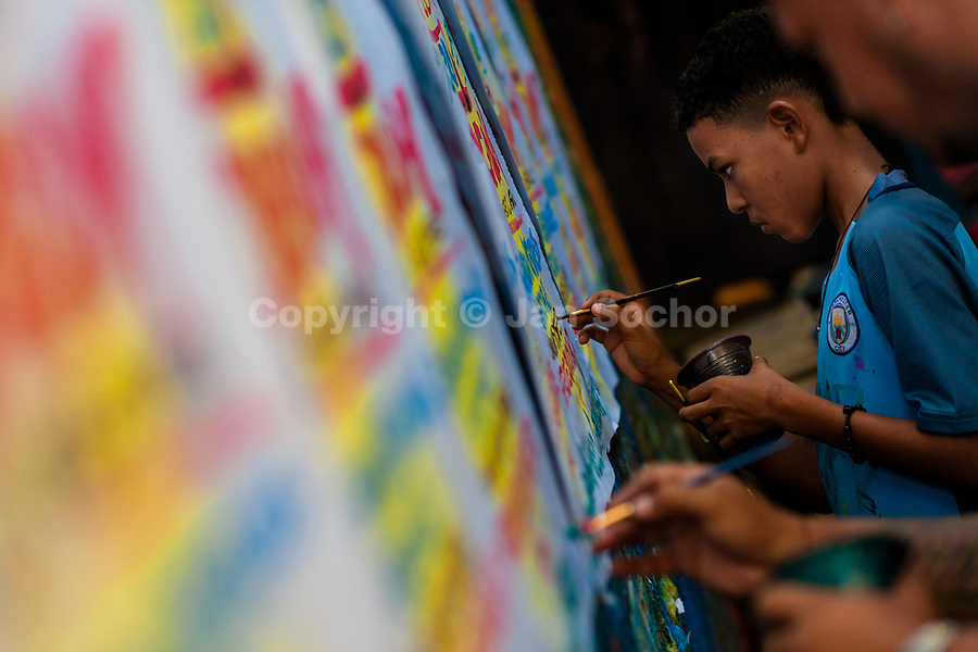"A Colombian sign painter apprentice writes with a brush while working on music party posters in the sign painting workshop in Cartagena, Colombia, 14 April 2018. Hidden in the dark, narrow alleys of Bazurto market, a group of dozen young men gathered around José Corredor (""Runner""), the master painter, produce every day hundreds of hand-painted posters. Although the vast majority of the production is designed for a cheap visual promotion of popular Champeta music parties, held every weekend around the city, Runner and his apprentices also create other graphic design artworks, based on brush lettering technique. Using simple brushes and bright paints, the artisanal workshop keeps the traditional sign painting art alive."