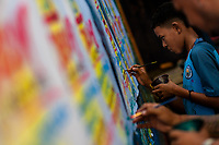"""A Colombian sign painter apprentice writes with a brush while working on music party posters in the sign painting workshop in Cartagena, Colombia, 14 April 2018. Hidden in the dark, narrow alleys of Bazurto market, a group of dozen young men gathered around José Corredor (""""Runner""""), the master painter, produce every day hundreds of hand-painted posters. Although the vast majority of the production is designed for a cheap visual promotion of popular Champeta music parties, held every weekend around the city, Runner and his apprentices also create other graphic design artworks, based on brush lettering technique. Using simple brushes and bright paints, the artisanal workshop keeps the traditional sign painting art alive."""