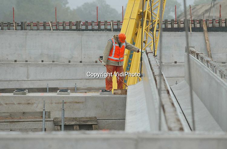 Foto: VidiPhoto..ANDELST - Op de plek waar de snelweg A15 tijdelijk enkele kilometers verlegd is, het Betuwse Andelst bij knooppunt Valburg, zijn de eerste betonnen leggers van 30 meter aangebracht voor een nieuw 57 meter lang viaduct. Ter plaatse is de situatie ingrijpend veranderd. Voorheen werd de A15 via een brug over de regionale verbindingsroute geleid. Straks is het precies andersom en gaat het regionale verkeer over het viaduct en het verkeer van de A15 er onderdoor. In de Betuwe ontstaan steeds meer irritatie over de werkzaamheden rond de A15 en de Betuwelijn. Behalve dat er veel wegen en viaducten worden afgesloten zorgt ook het werkverkeer voor een grote problemen rond de verkeersveiligheid in en rond de dorpen.
