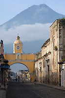 Looking south down the Calle Real in the beautiful Spanish colonial city of Antigua, Guatemala, towards the Santa Catalina Arch and the Agua Volcano.