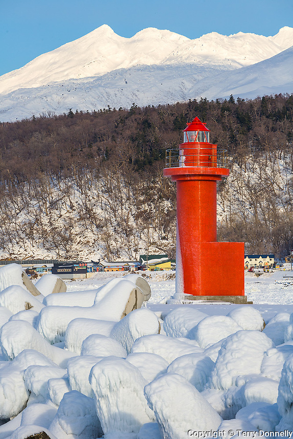 Hokkaido Island, Japan<br /> Red port lighthouse at the Utoro fishing village pier, on the Shiretoko Peninsula