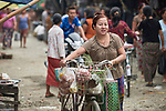 A woman pushes a bicycle through the Tahan Market in Kalay, a town in Myanmar. This market is located in Tahan, the largely ethnic Chin section of the town. The woman is wearing thanaka, a cosmetic paste, on her face.