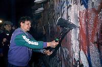 Berlino, 9 Novembre, 1989. Giovani Tedeschi durante le manifestazioni che hanno portato alla caduta del muro di Berlino. A man attacks the Berlin Wall with a pickaxe