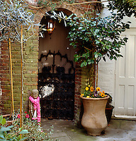 A carved wooden figure with a garland of flowers around its neck stands by a brick archway in the courtyard garden