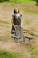 Young woman standing in field next to empty adirondack chair