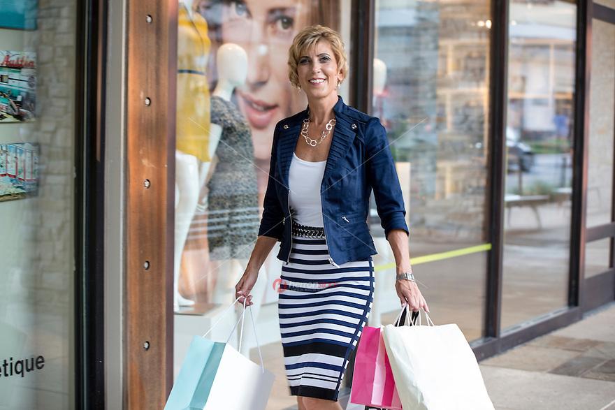Fashionable female shopper walks down the sidewalk at an Austin outdoor shopping mall, Austin, Texas.
