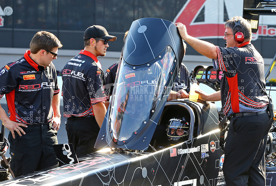 Sep 18, 2015; Concord, NC, USA; NHRA top fuel driver Shawn Langdon sits beneath the canopy in his dragster with crew members alongside during qualifying for the Carolina Nationals at zMax Dragway. Mandatory Credit: Mark J. Rebilas-USA TODAY Sports