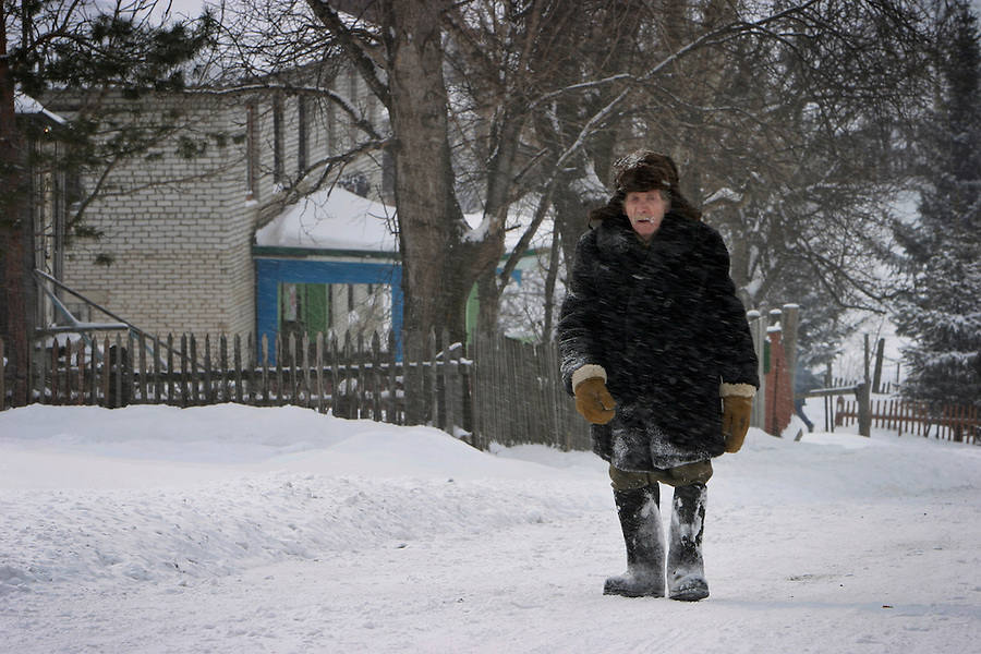 Malishevo, Russia, 29/02/2004.&amp;#xD;An old man struggkes uphill to the village centre during a snow blizzard.<br />