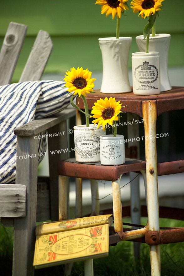 Antique and collectible stores offer all manner of everyday objects that can find new life as vases and stem holders for flowers.  Here, single stems of sunflowers rest in old British crocks set out on a well-used stepladder.  A wooden bench, striped ticking pillow, and a good book complete the backyard scene.