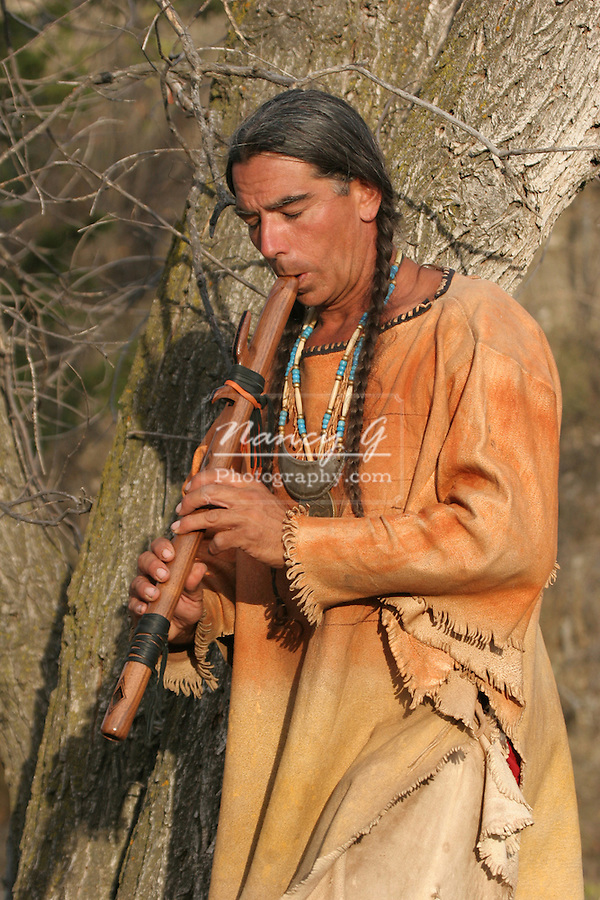 A Native American Indian man playing a musical flute