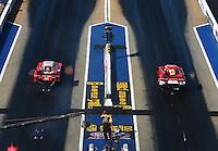 Jun 17, 2016; Bristol, TN, USA; NHRA funny car driver Cruz Pedregon (left) races alongside Chad Head during qualifying for the Thunder Valley Nationals at Bristol Dragway. Mandatory Credit: Mark J. Rebilas-USA TODAY Sports
