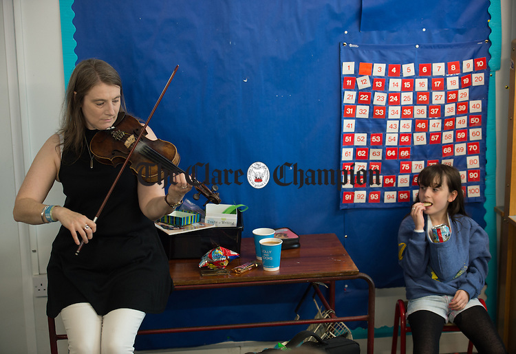 Jackie Deeveney of St James The Great CCE, Glasgow getting in some last minute practice  before competition as her daughter Aoife tucks into to her Taytos during Fleadh Cheoil na hEireann in Ennis. Photograph by John Kelly.