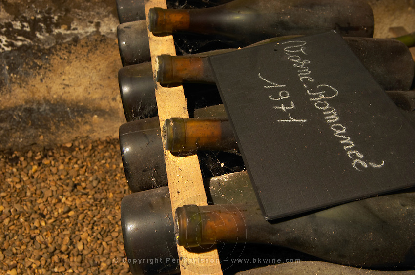 In the underground wine cellar: a pile of bottles of Vosne Romanee Romanée 1971 red Burgundy wine with the appellation written in white text on a black chalkboard chalk board on a gravelly pebbly soil, Maison Louis Jadot, Beaune Côte Cote d Or Bourgogne Burgundy Burgundian France French Europe European